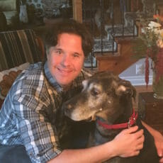 Veterinarian hugging large black and grey dog
