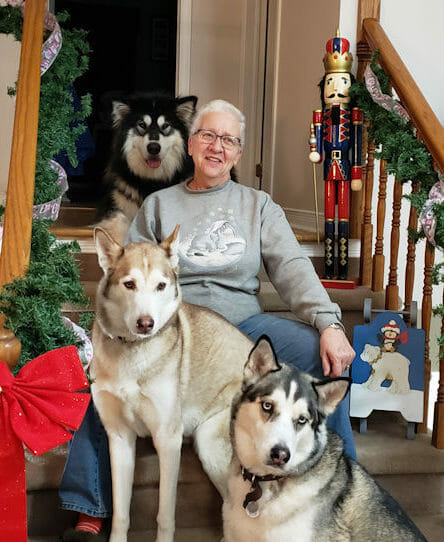 Client care representative sitting on the stairs surrounded by three huskies