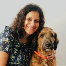Veterinarian standing next to black and brown dog with her arm around the dog