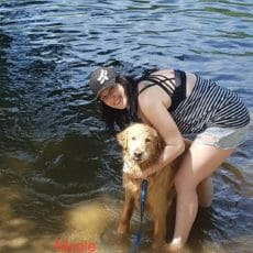Client care representative standing next to a wet dog in the water